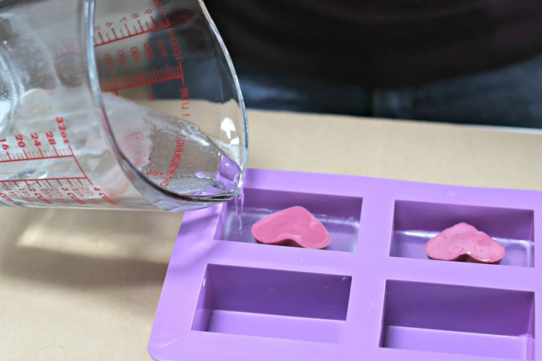 DIY Valentine soap pouring clear soap around pink hearts
