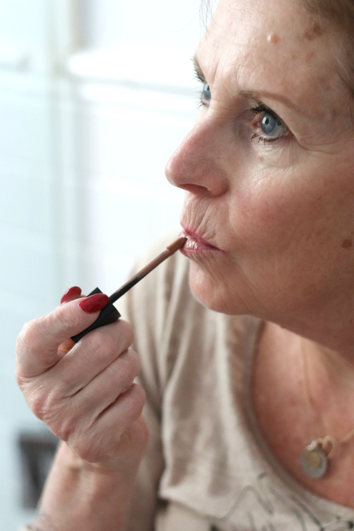 TSC July Beauty Tote mom applying SKINN Caviar Lip Cream